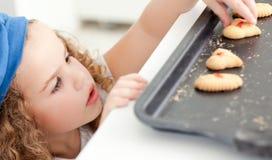 Petite fille volant des biscuits photographie stock
