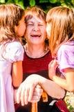Petite-filles embrassant leur vieille grand-mère photographie stock