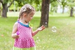 Petite jolie fille dans une robe lumineuse jouant avec des bulles de savon en parc d'été Attrape des bulles de savon Image libre de droits