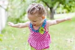 Petite jolie fille dans une robe lumineuse jouant avec des bulles de savon en parc d'été Attrape des bulles de savon Images stock