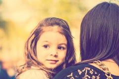 Petite jolie fille marchant sur la rue de ville avec la mère Photographie stock