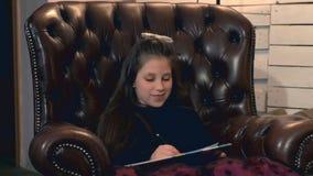 Petite jolie fille peignant un tableau se reposant dans un fauteuil en cuir banque de vidéos