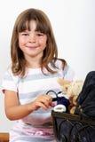 Petite jolie fille poussant une poussette de poupée Photo stock