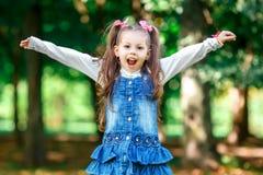 Petite la fille gaie et heureuse avec des bras tendus été dans une robe bleue dehors en parc sourit gentiment Image libre de droits