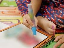 Petite main asiatique du ` s de bébé tenant le grand stylo de couleur pour faire la peinture photos stock