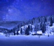 Petite maison en bois dans un paysage de montagne d'hiver de nuit Photos stock