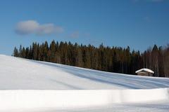 Petite maison en bois en hiver. Image stock