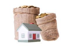 Petite maison et sacs de jouet avec de l'argent. Photo libre de droits