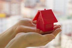 Petite maison rouge dans des mains Photos stock