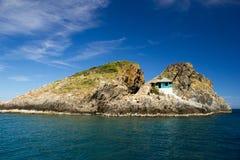 Petite maison sur les roches en mer Images libres de droits