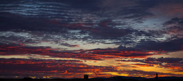 Petite maison vide sous les nuages rouge-oranges au coucher du soleil photo stock