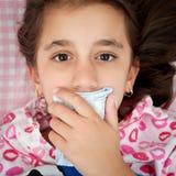 Petite malade de fille avec le revêtement de grippe sa bouche Photo stock
