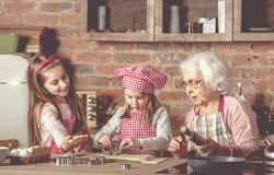 Petite mamie d'aide de petite-filles pour faire des biscuits cuire au four images libres de droits