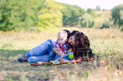 Petite mom and son. Mom and son lying on the grass in the forest stock images
