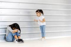 Petite moquerie asiatique de fille à une fille asiatique plus âgée qui se reposent et bas sa tête sur le plancher, mur blanc derr photographie stock libre de droits