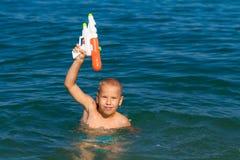 Petite natation heureuse de garçon en mer avec l'enfance heureux de concept d'arme à feu d'eau photographie stock