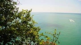 Petite navigation blanche de bateau de la côte des eaux de mer azurées à l'horizon Photos stock