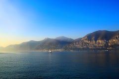 Petite navigation blanche de bateau sur le lac sur un beau coucher du soleil Images libres de droits