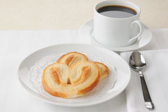 Petite Palmiers with coffee. Two petite palmiers with a cup of coffee royalty free stock photo