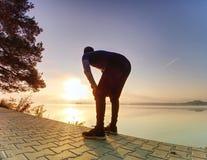 Petite pause pour le souffle Silhouette d'homme actif sur la plage de lac images stock