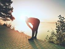 Petite pause pour le souffle Silhouette d'homme actif sur la plage de lac images libres de droits