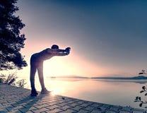 Petite pause pour le souffle Silhouette d'homme actif sur la plage de lac image libre de droits