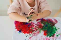 Petite peinture asiatique de fille avec le pinceau et les peintures colorées Images stock