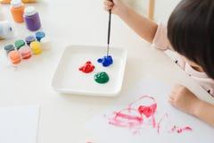Petite peinture asiatique de fille avec le pinceau et les peintures colorées Image libre de droits