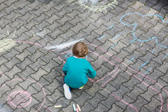 Petite peinture blonde de garçon avec les craies colorées dehors Image libre de droits