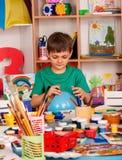 Petite peinture de garçon d'étudiants dans la classe d'école d'art Photos libres de droits