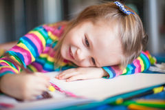 Petite peinture mignonne de fille avec des crayons tandis que Images stock