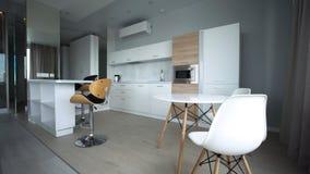Petite pièce moderne avec le secteur de cuisine et le plancher en bois Intérieur à la mode moderne de cuisine photographie stock libre de droits