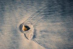 Petite pierre en sable de plage photographie stock libre de droits