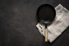 Petite poêle dosée vide sur une table en pierre noire Fond à cuire foncé image stock