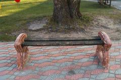 Petite position de banc de ville sur un trottoir pr?s d'un arbre images stock