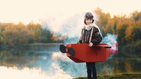 Petite position heureuse de fille d'aviateur au lac de coucher du soleil dans le costume plat de carton avec de la fumée de coule clips vidéos