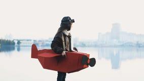 Petite position heureuse de fille d'aviateur au panorama de ville de lac de coucher du soleil dans le costume plat de carton joua banque de vidéos