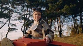 Petite position heureuse de garçon d'aviateur sous des arbres dans le costume plat de carton avec des verres de cru jouant le mou banque de vidéos