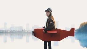 Petite position pilote heureuse de fille au panorama calme de ville de lac dans l'avion de carton jouant l'aviateur regardant le  banque de vidéos