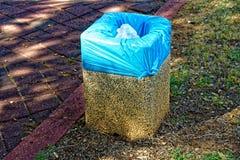 Petite poubelle de pierres avec un sac de déchets bleu Photo libre de droits
