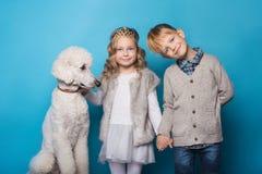 Petite princesse et garçon beau avec le caniche royal Amour Amitié famille Portrait de studio au-dessus de fond bleu Image libre de droits