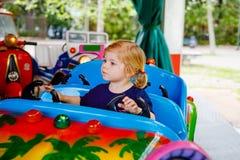 Petite ?quitation adorable de fille d'enfant en bas ?ge sur la voiture dr?le sur le carrousel de rond point en parc d'attractions photo libre de droits