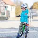 Petite équitation préscolaire de garçon d'enfant avec son premier vélo vert Photographie stock libre de droits