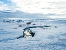 Petite rivière au milieu de neige pendant l'hiver Photos stock