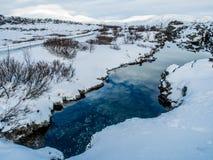 Petite rivière au milieu de neige pendant l'hiver Image libre de droits