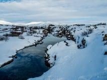 Petite rivière au milieu de neige pendant l'hiver Image stock