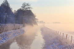 Petite rivière congelée entre les champs et les forêts pendant le crépuscule dans les WI Photographie stock