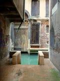 Petite rue dans Venezia avec l'accès au canal Images libres de droits
