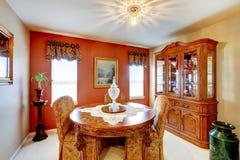 Petite salle à manger avec le mur rouge d'accent, et Vieux Monde détaillé s photo stock