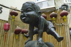 Petite sculpture jouante heureuse en garçon de point de repère de la concession française à Changhaï central, Chine photographie stock libre de droits